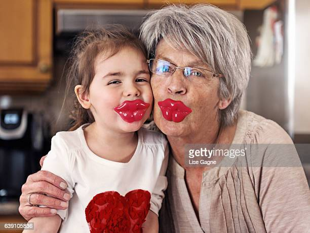 little girl and grandmother posing with big lips lollypop - big lips stock photos and pictures