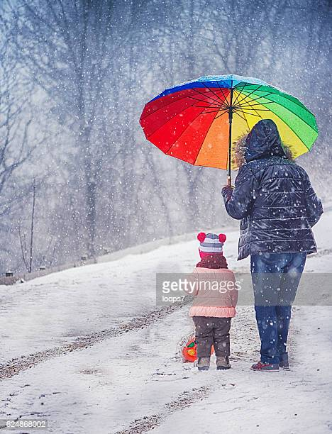 Little Girl and Grandmother With Umbrella in the Winter