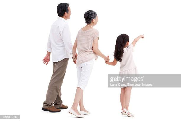 Little girl and grandparents, pointing the front