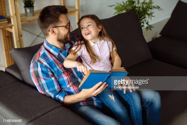 Little girl and her father reading a book at home