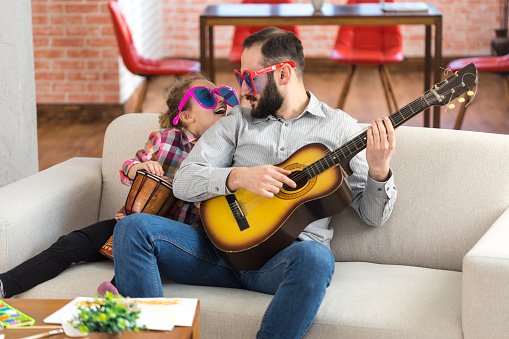 Little girl and her father with funny sunglasses playing instruments 1010054822