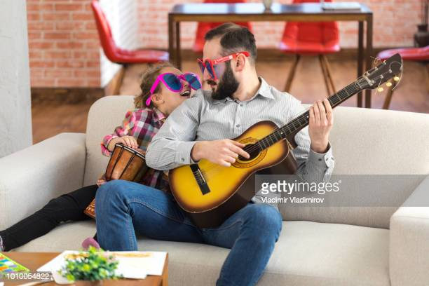 little girl and her father with funny sunglasses playing instruments - fathers day stock pictures, royalty-free photos & images