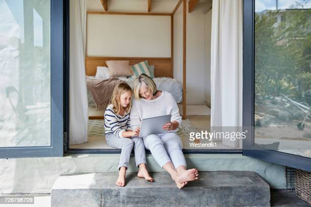 little girl and her grandmother using tablet - harmony stock pictures, royalty-free photos & images