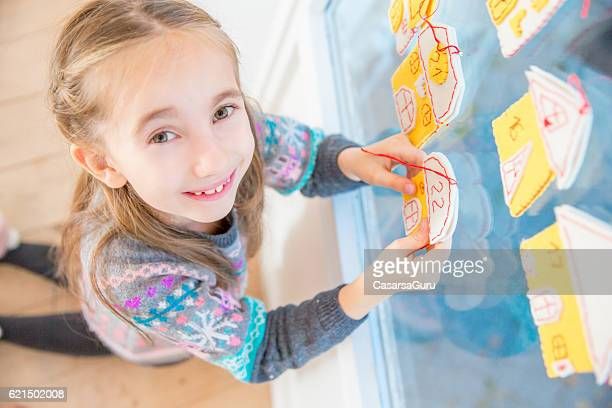 Little Girl and her Homemade Advent Calendar on Window