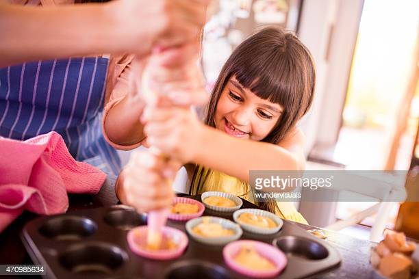 Kleine Mädchen und ihre Mutter machen cupcakes zusammen