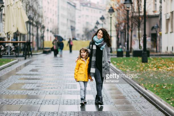 little girl and her mom walking through the city - aunt stock pictures, royalty-free photos & images
