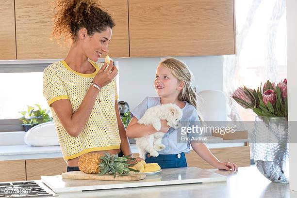 little girl and her mother eating pineapple in the kitchen - dog eats out girl stock pictures, royalty-free photos & images