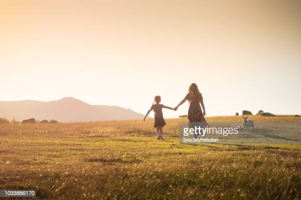 little girl and her mother going for walk through the rural sunset pastures of keswick, england - keswick stock photos and pictures