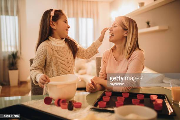 Little girl and her mother having fun while making a cake at home.
