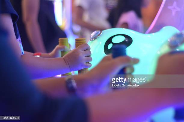 Little girl and her mother holding arcade machine game's joystick