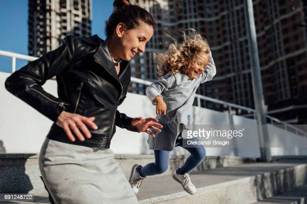 Little girl and her mother jumping from concrete steps in a modern urban environment