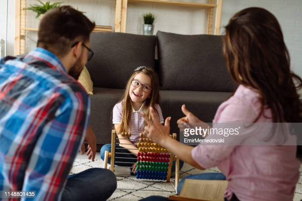 Little girl and her parents learning mathematics at home using abacus