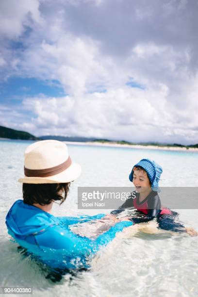 Little girl and mother playing in shallow tropical water, Japan