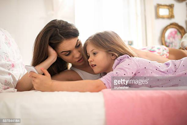 Little girl and mother using mobile phone in bedroom.