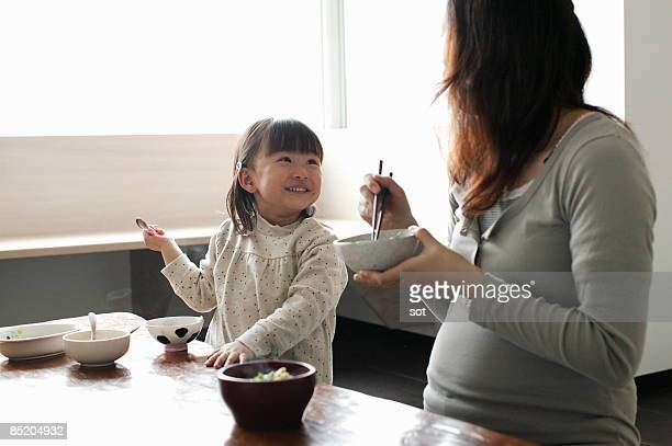 Little girl and pregnant mother eating meal