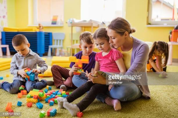 kleine mädchen und vorschule lehrer lesen eines buches im kindergarten. - kindergarten stock-fotos und bilder