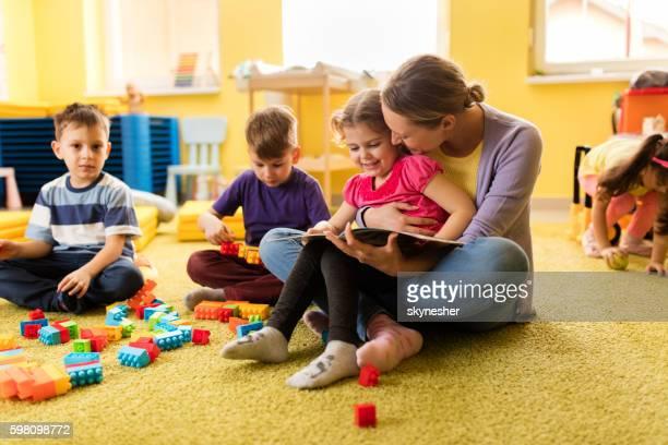 Little girl and preschool teacher reading a book at kindergarten.