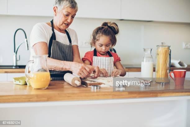 Kleine Mädchen und Senior Frau gemeinsam Cookies machen