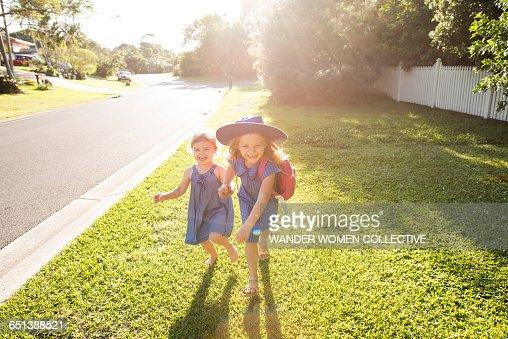 Little girl and sister walking to school Australia