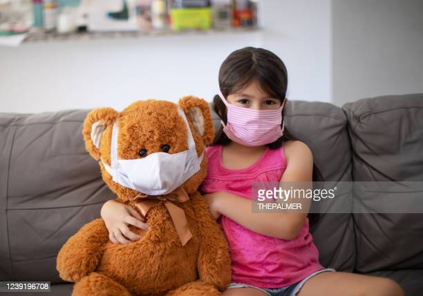little girl and teddy bear smiling behind the mask - new normal stock pictures, royalty-free photos & images