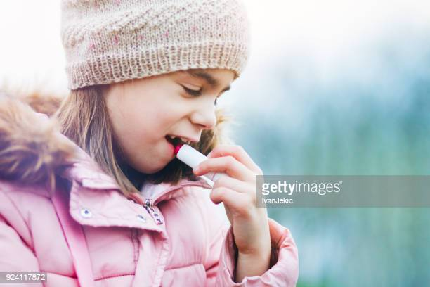 little girl applying a protective lip balm - lip balm stock pictures, royalty-free photos & images