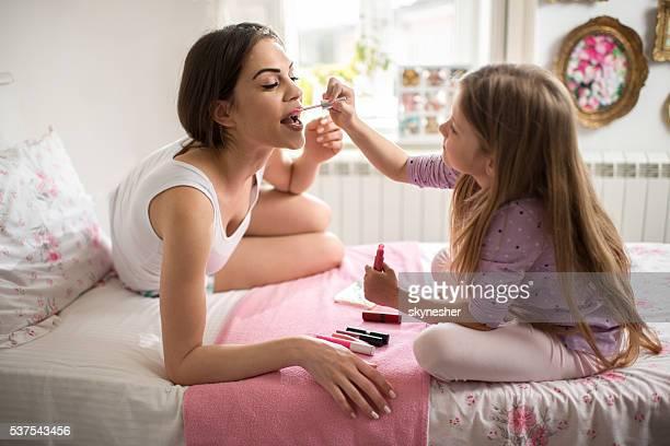 Kleines Mädchen Lipgloss anwenden am Mutter- Lippen im Schlafzimmer.
