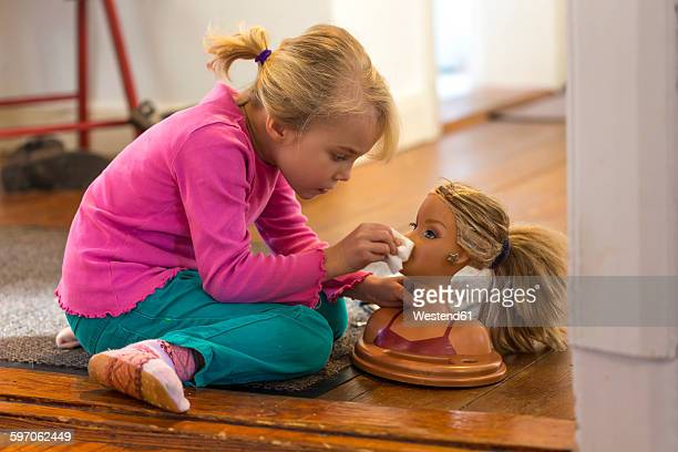 little girl applying make up on her doll - girl chest stock photos and pictures