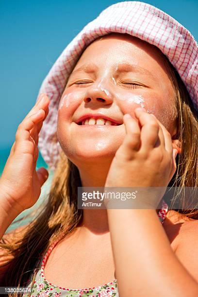 Little girl applying sun-protection lotion