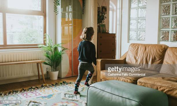 little girl approaches a glass interior doorway - domestic life stock pictures, royalty-free photos & images