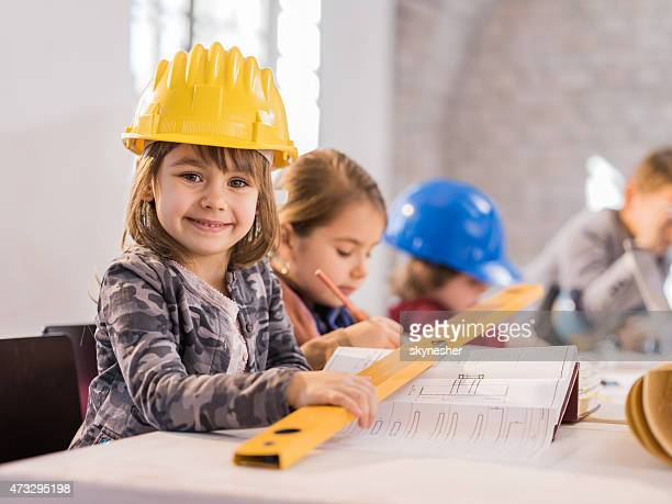 Little girl architect smiling and looking at camera.