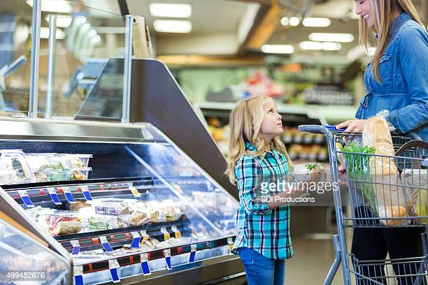 Little girl asking mom for something while grocery shopping