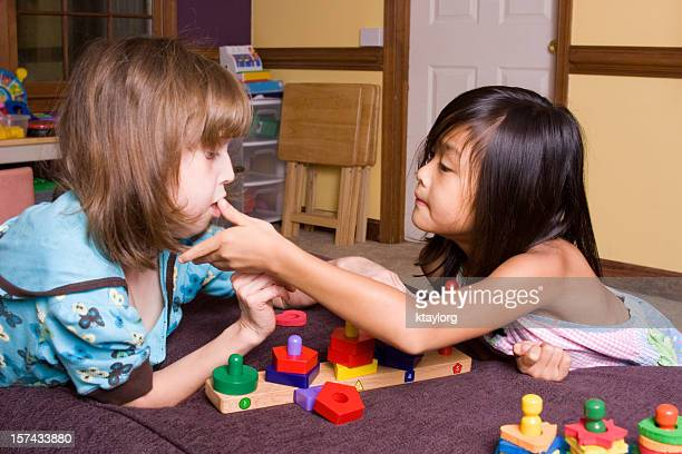Little girl assisting her autistic sister