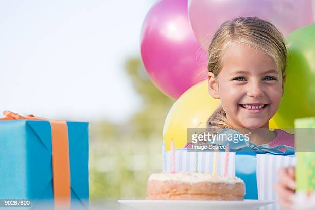 Little girl at her birthday party with cake, presents and colourful balloons