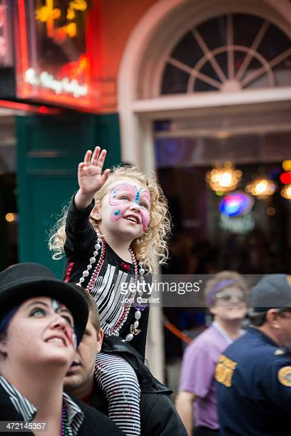 little girl at mardi gras on father's shoulders - mardi gras girls stock photos and pictures