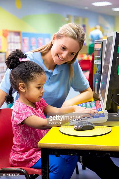 Little girl at nusery learning new technology with teacher.