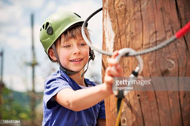 Little girl attaching a carabiner to zip line