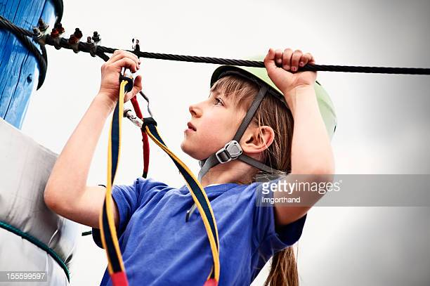 Little girl attaching a carabiner to zip line.