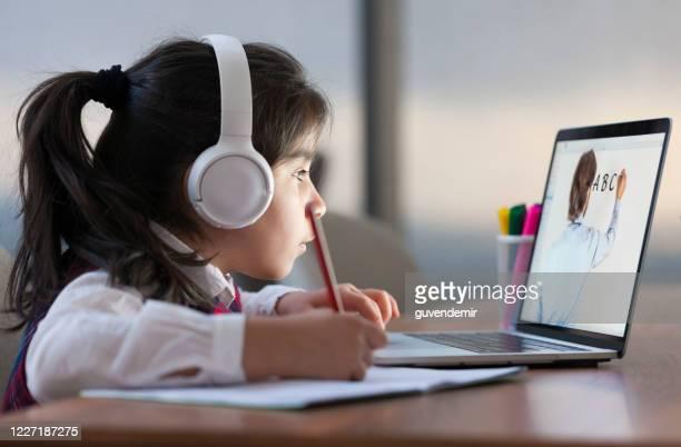petite fille s'occupant de la classe d'école en ligne - classe virtuelle photos et images de collection