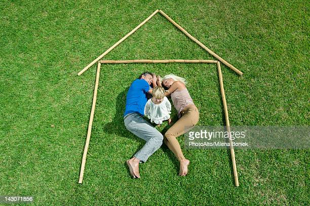 Little girl awake, parents sleeping, together within outline of house, high angle view