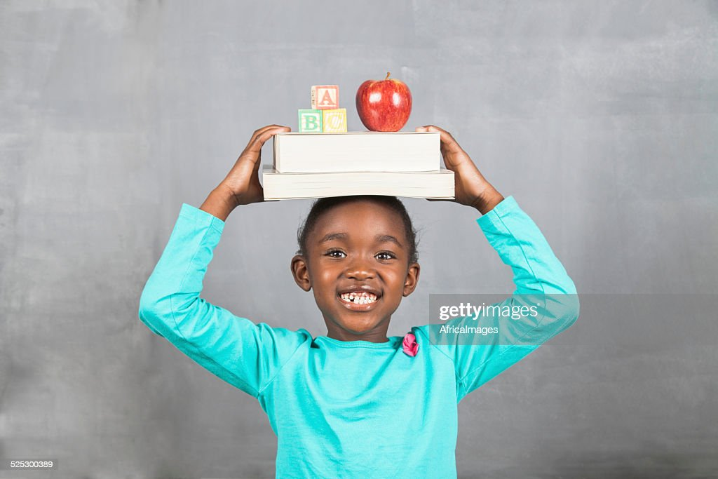 Little girl balancing books and an apple on her head : Stock Photo