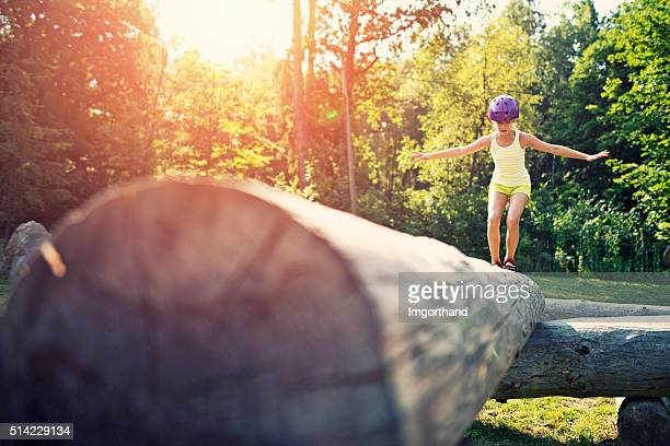 little girl balancing on a trunk in adventure park - obstacle course stock photos and pictures