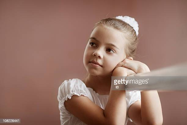 Little Girl Ballerina Holds onto Ballet Bar