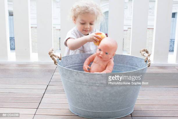 Little girl bathing baby doll in bucket outdoors