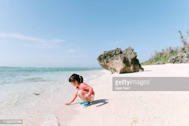 Little girl beachcombing on idyllic tropical beach, Okinawa, Japan