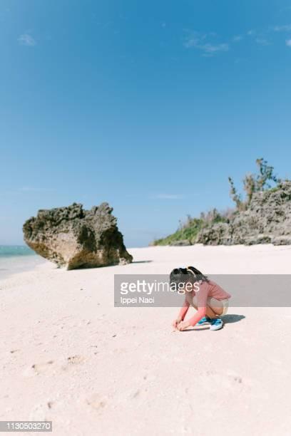 Little girl beachcombing on tropical beach, Okinawa, Japan