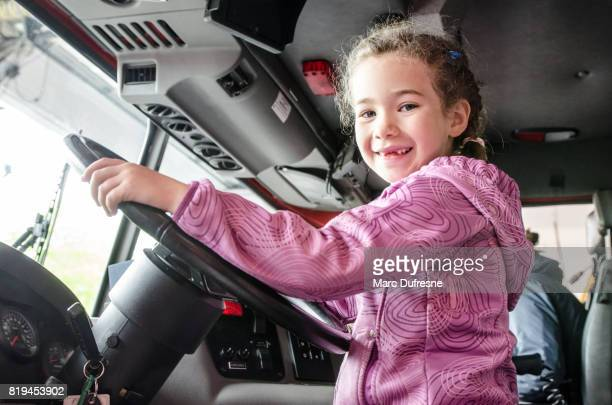 little girl behind firetruck steering wheel - firetruck stock photos and pictures