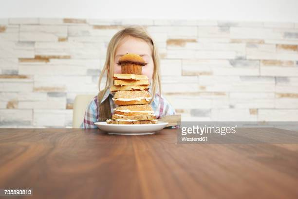 Little girl behind stack of baked goods