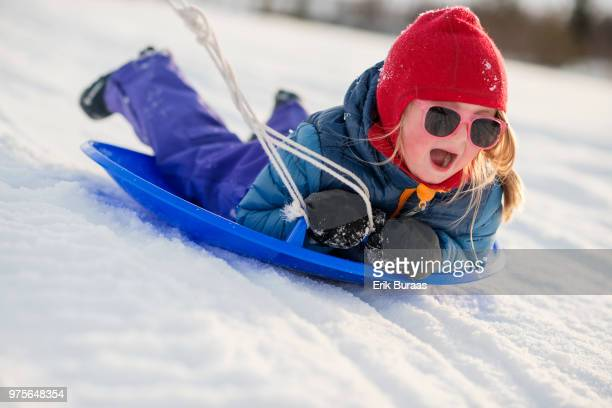 Little girl being pulled on a toboggan