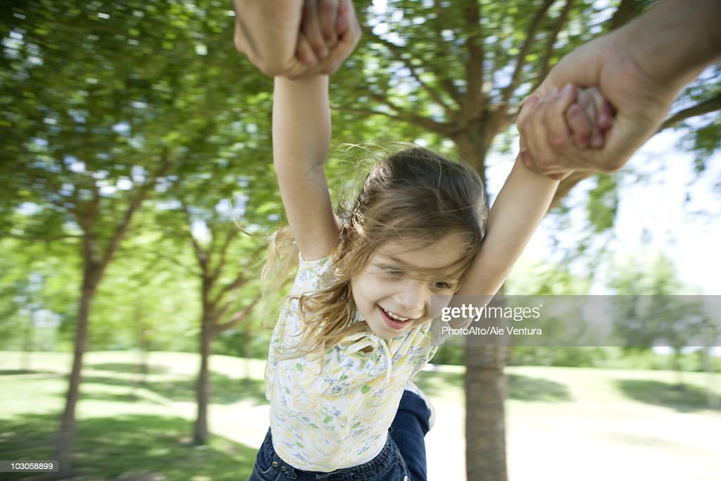 Little girl being swung through air by her arms : Stock Photo