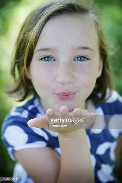 A little girl blowing a kiss to the camera
